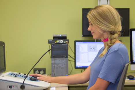 RESEARCH ASSISTANT SEATED AT AN AUDIOMETER TO PERFORM HEARING TESTING